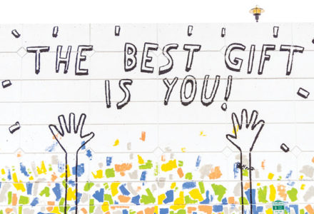 Illustration of 2 hands presenting the title, 'The Best Gift Is You' with blue, green yellow and grey confetti for the blog post, 'Why You Are Beautiful Just The Way You Are'