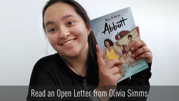 Photograph of Olivia Simms holding up her published story, 'How to be an Abbott'