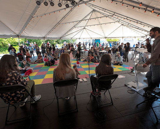 Photograph of presenters sitting in front of a group of students inside a big tent