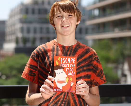 Photograph of Christopher holding his book, 'Escape From The Taco Shop'