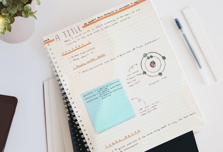 A neatly organized page of notes sits on a white desk. A pen is next to the notebook