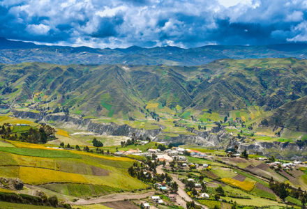 The vibrant green Andes Mountains are set against a blue and grey cloudy sky in Ecuador.