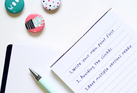 A pen lays flat on a notepad. Both objects are on a diagonal atop a white desk.