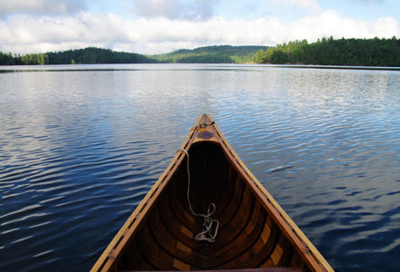 The bow of a canoe looks out onto open blue water. There are some green hills with trees on them in the distance.