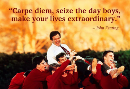 A quote from Dead Poets Society is displayed on screen, along with John Keating (Robin Williams) being carried on the shoulders of his students. Keating is wearing a white dress shirt and tie, while the boys are wearing matching red blazers.