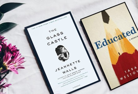 Two memoirs, Jeannette Walls' The Glass Castle and Tara Westover's Educated, lay on a table. The Glass Castle features a white cover and a black border with a girl cupping her hand around her mouth as if she is whispering to an unseen somebody. Educated features the tip of a pencil.