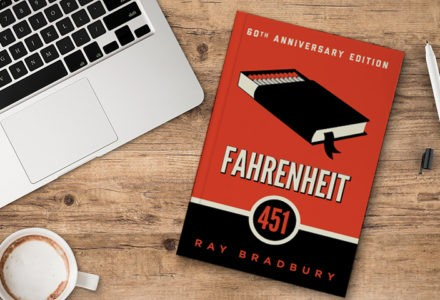 Ray Bradbury's Fahrenheit 451 sits on a desk with a laptop and a mug. The cover is red and black and features a black book.