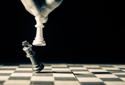 The final move on a chess board is made to denote a loss. A white piece knocks over a black piece to end the game.