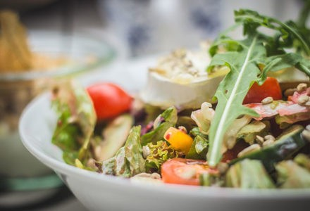A salad with lettuce, tomatoes and zucchini sits in a bowl.