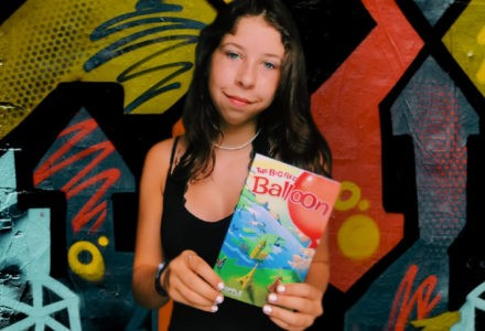 Mya Barnett, winner of the Kids Write 4 Kids Contest, poses with her newly-published book, The Big Red Balloon.