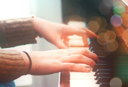 fingers are laid gently on the keys of a piano.