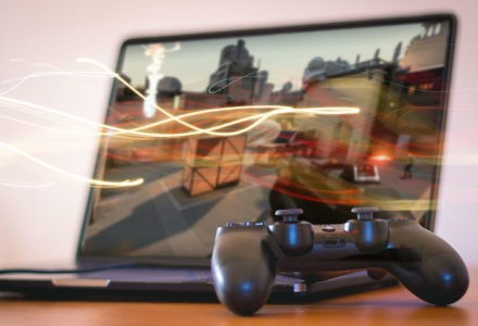 A gaming controller sits in front of a laptop with glowing energy rays coming out of it.