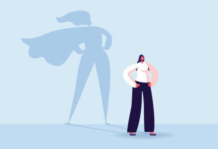 A woman poses with hands on her hips. Her shadow is wearing a cape to say that she's a superhero.